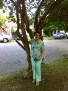 Mom sitting in the crook of a crepe myrtle tree