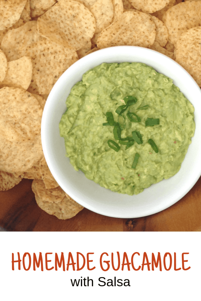white bowl of homemade guacamole with salsa nestled in a wooden bowl of tortilla chips