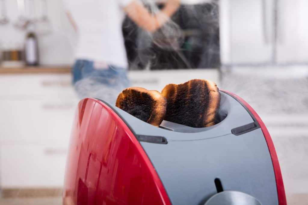 Close-up of Burnt Toast Coming Out of Toaster in Kitchen: Dinner Party Mistakes