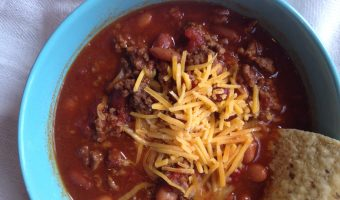 Chili in a blue bowl with a chip and cheese sprinkled on top