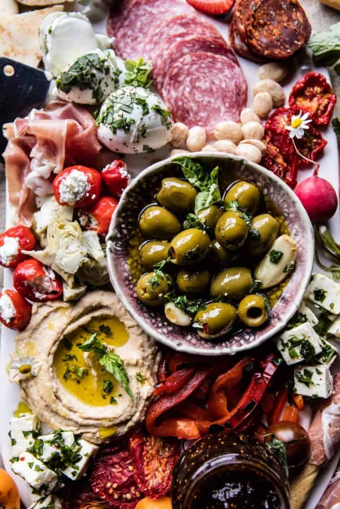 an arrangement of food including fresh mozzarella, salami, ham, cherry tomatoes stuffed with feta, hummus, and olives
