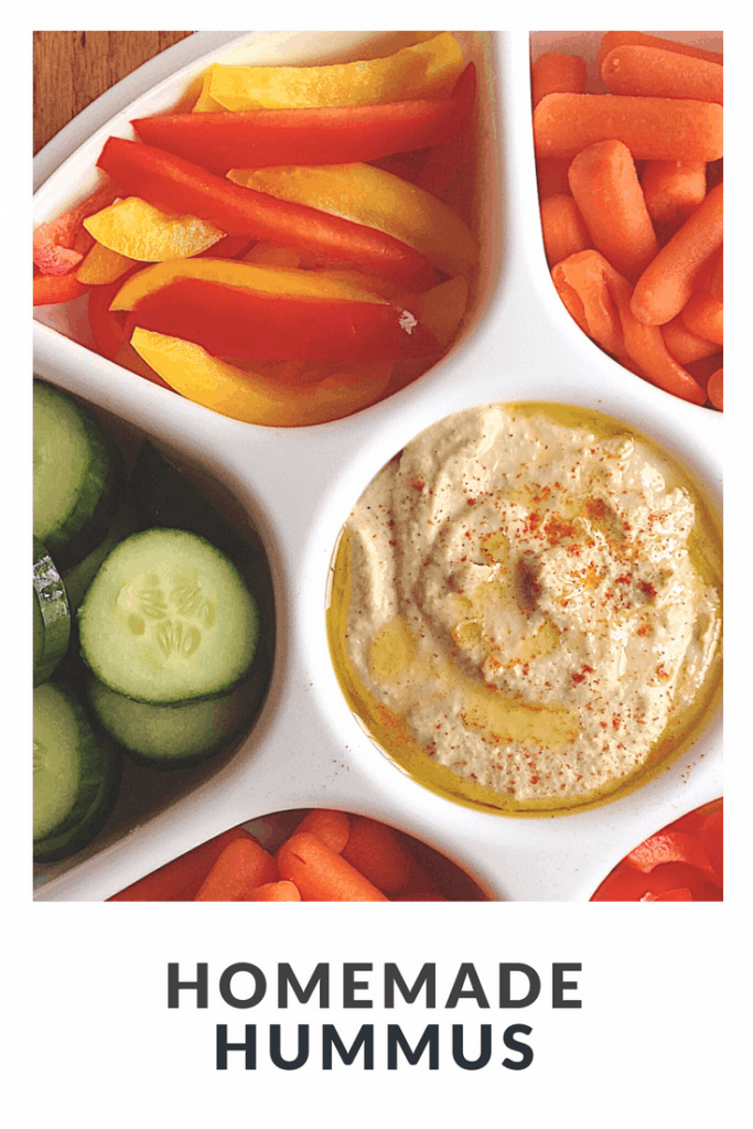white vegetable tray with hummus, cucumbers, bell peppers, and carrots