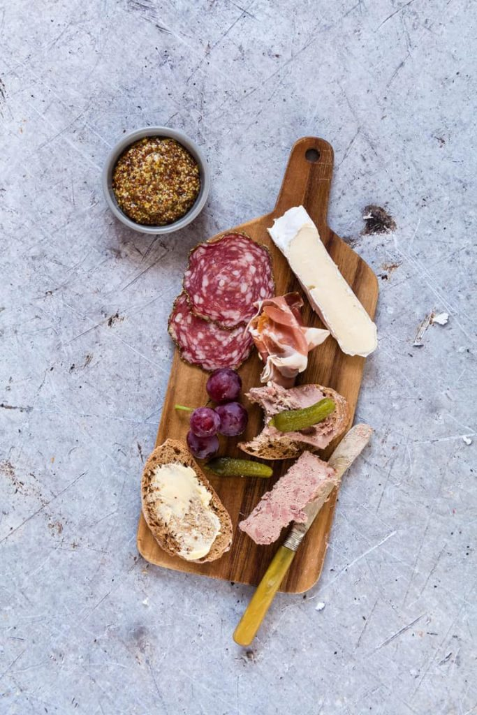 wooden board with pate, salami, grapes, brie cheese and baguette