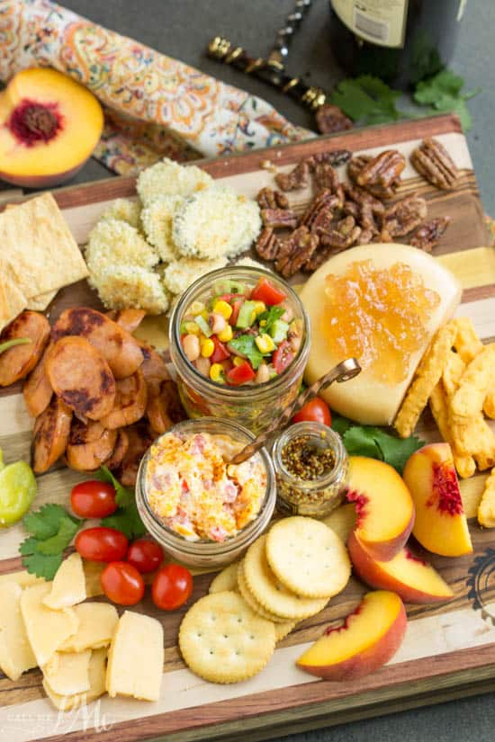 wooden board with an assortment of cheeses, smoked sausage, pimento cheese, black eyed pea salad, fried zucchini, pecans, peaches, and crackers