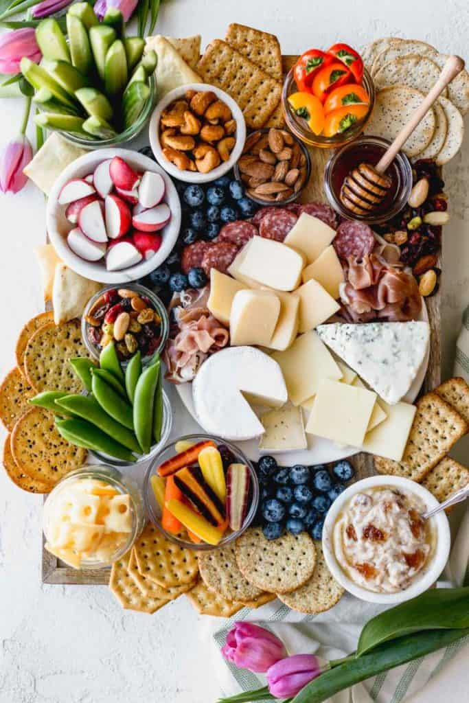 charcuterie board with cheeses, dried meats, crackers, radishes, nuts, and honey