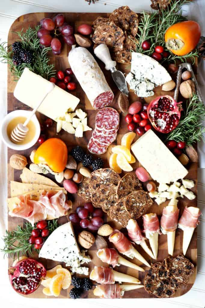 charcuterie board with prosciutto and blue cheese-wrapped pears, bread, cheeses, cured meats