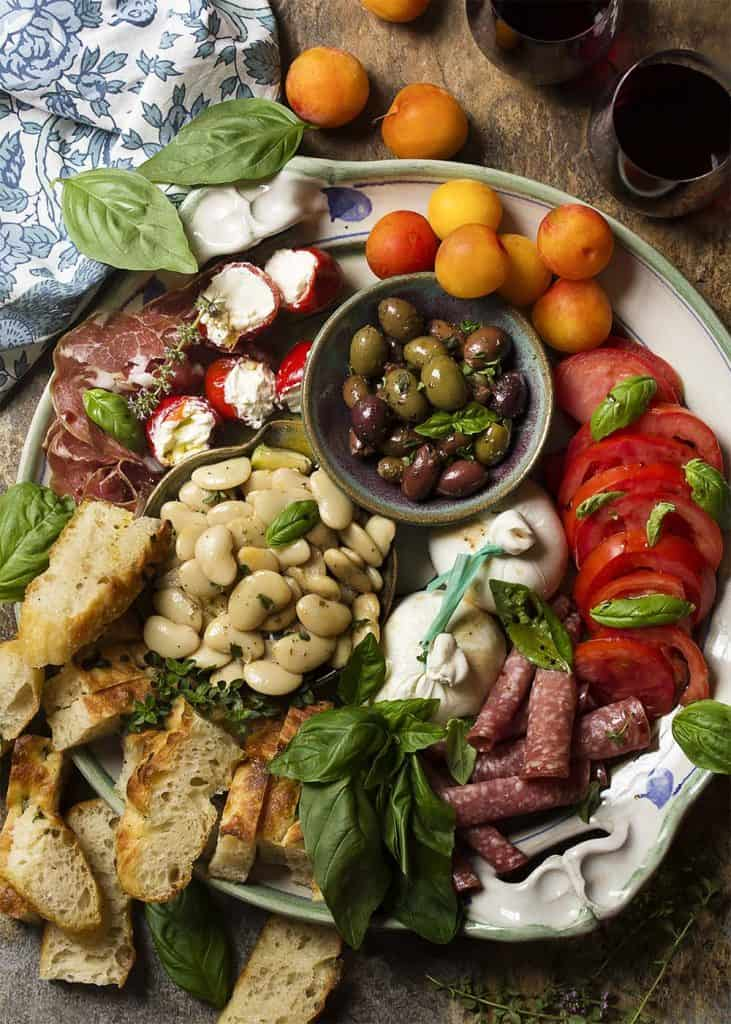 charcuterie board with fresh tomatoes, fresh mozzarella, white bean salad, baguette, cherry tomatoes, and cured meats