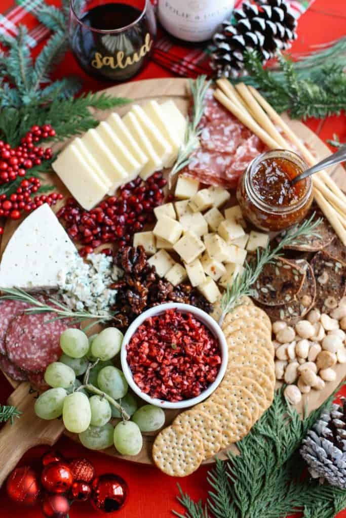 holiday charcuterie board featuring pomegranate, cheese, cured meats, jelly, and crackers