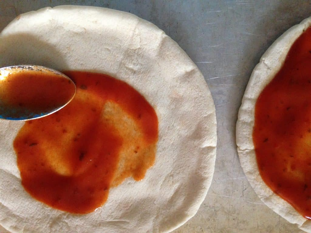 pita bread on a baking sheet with a spoon spreading pizza sauce