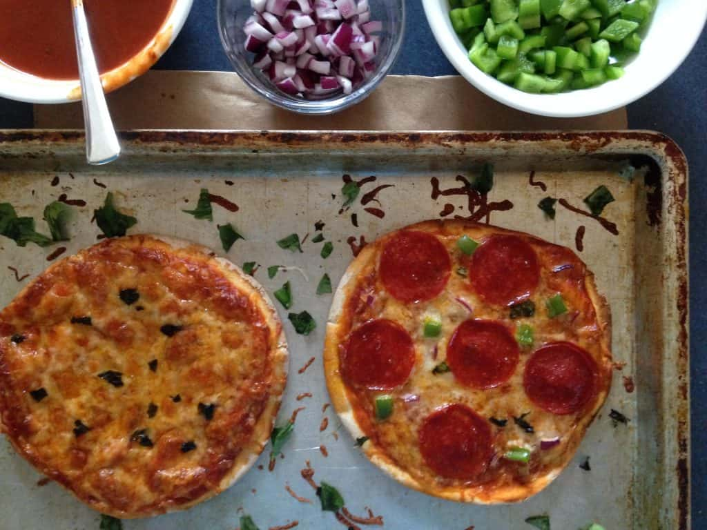 two baked pita pizzas with a bowl of sauce, a bowl of red onion, and a bowl of green peppers