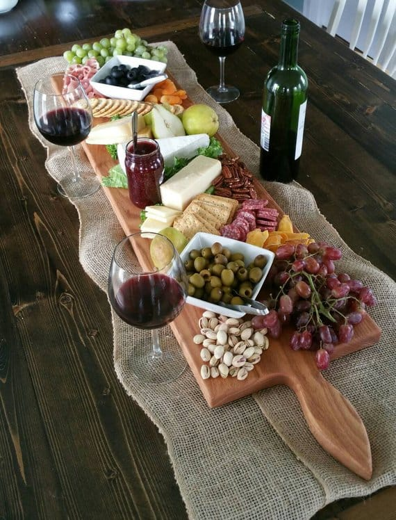 long charcuterie board with glasses of wine sitting beside