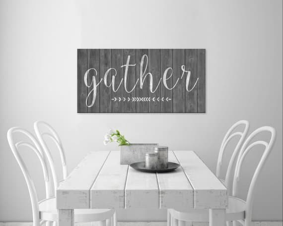"white table and chairs with a gray sign that says ""gather"""