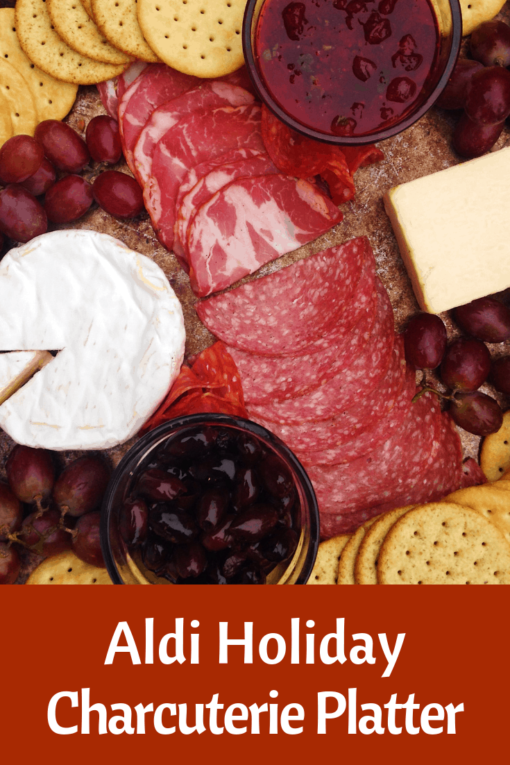 holiday charcuterie board with camembert, aged cheddar, 3 cured meats, crackers, black olives, and grapes