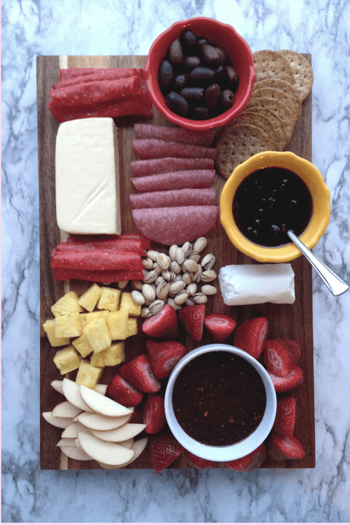 cheese/chocolate charcuterie board filled with meats, olives, jam,  and fruit.