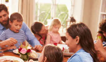 a group of parents and kids sitting around a table eating