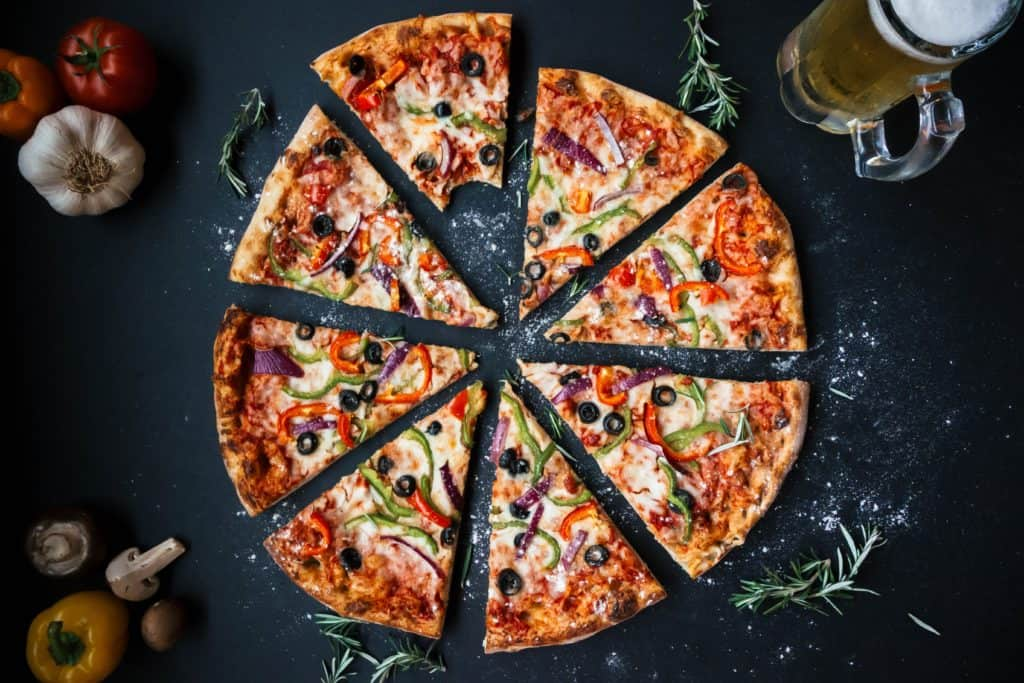 pizza with cut with olives and vegetables on top